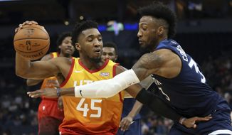 Utah Jazz's Donovan Mitchell controls the ball against Minnesota Timberwolves' Robert Covington in the first half of an NBA basketball game Wednesday, Dec. 11, 2019, in Minneapolis. (AP Photo/Stacy Bengs)