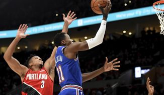 New York Knicks guard Frank Ntilikina, left, drives to the basket on Portland Trail Blazers guard CJ McCollum, right, during the first half of an NBA basketball game in Portland, Ore., Tuesday, Dec. 10, 2019. (AP Photo/Steve Dykes)