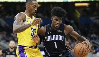 Orlando Magic's Jonathan Isaac (1) looks for a path to the basket against Los Angeles Lakers' Dwight Howard, left, during the second half of an NBA basketball game, Wednesday, Dec. 11, 2019, in Orlando, Fla. (AP Photo/John Raoux)