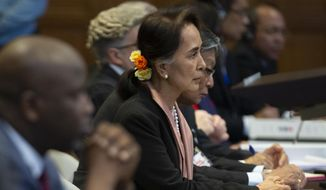 Myanmar's leader Aung San Suu Kyi and Gambia's Justice Minister Aboubacarr Tambadou, left, listen to judges in the court room of the International Court of Justice for the first day of three days of hearings in The Hague, Netherlands, Tuesday, Dec. 10, 2019. Aung San Suu Kyi will represent Myanmar in a case filed by Gambia at the ICJ, the United Nations' highest court, accusing Myanmar of genocide in its campaign against the Rohingya Muslim minority. (AP Photo/Peter Dejong)