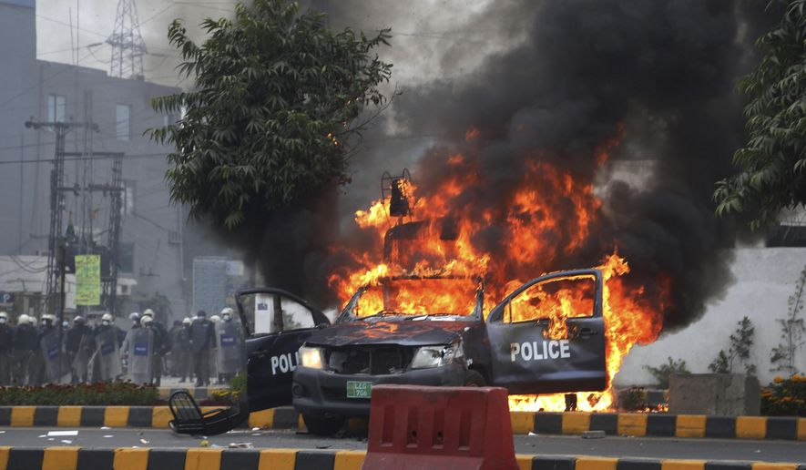 Police officers gather next to a burning police vehicles that were set on fire by angry lawyers during clashes in Lahore, Pakistan, Wednesday, Dec. 11, 2019. Hundreds of Pakistani lawyers, angered over alleged misbehavior of some doctors toward one of their colleagues last month, stormed a cardiology hospital in the eastern city of Lahore, setting off scuffles with the facility's staff and guards that left heart patients unattended for several hours. (AP Photo/K.M. Chaudary)