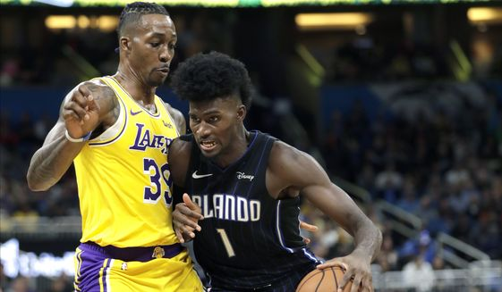 Orlando Magic's Jonathan Isaac (1) looks for a path to the basket against Los Angeles Lakers' Dwight Howard, left, during the second half of an NBA basketball game, Wednesday, Dec. 11, 2019, in Orlando, Fla. (AP Photo/John Raoux)  **FILE**