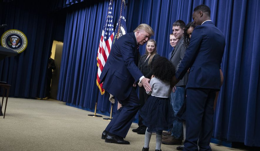 President Donald Trump greets families participating in the White House Summit on Child Care and Paid Leave in the South Court Auditorium on the White House complex, Thursday, Dec. 12, 2019, in Washington. (AP Photo/ Evan Vucci)