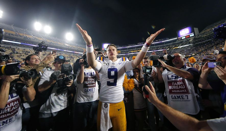 FILE - In this Nov. 30, 2019, file photo, LSU quarterback Joe Burrow (9) gestures thanks to the student section after playing his last game in Tiger Stadium, an NCAA college football game against Texas A&M, in Baton Rouge, La. LSU quarterback Joe Burrow is The Associated Press college football player of the year in a landslide vote.  Burrow, who has led the top-ranked Tigers to an unbeaten season and their first College Football Playoff appearance, received 50 of 53 first-place votes from AP Top 25 poll voters and a total of 156 points. (AP Photo/Gerald Herbert, File)