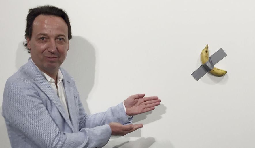 """FILE- In this Dec. 4, 2019 photo, gallery owner Emmanuel Perrotin poses next to Italian artist Maurizio Cattlelan's """"Comedian"""" at the Art Basel exhibition in Miami Beach, Fla. The work sold for $120,000. A Miami couple who bought a headline-grabbing banana duct-taped to a wall say they acknowledge the absurdity of the artwork, but believe it will become an icon and plan to gift it to a museum. (Siobhan Morrissey via AP)"""