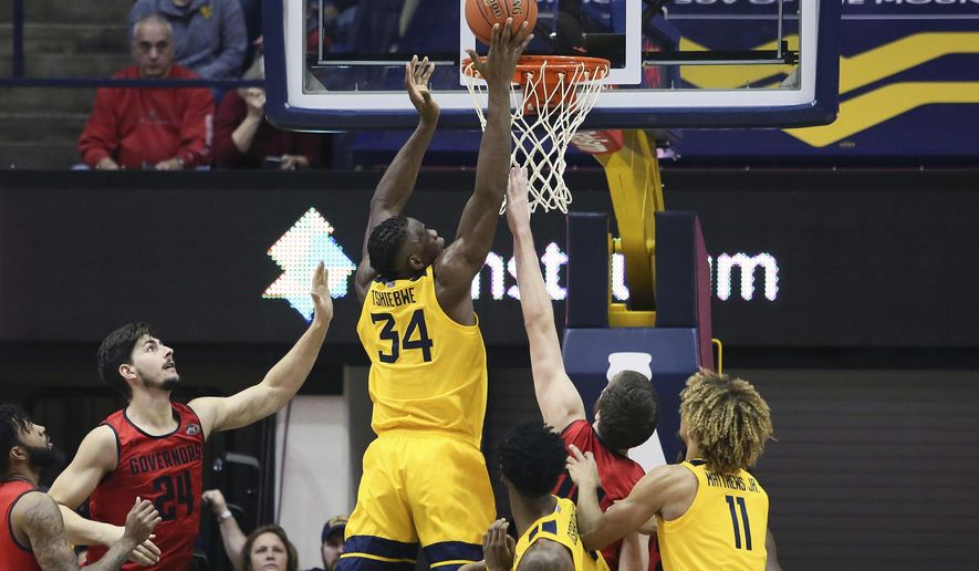 West Virginia forward Oscar Tshiebwe (34) makes a basket as he is defended by Austin Peay center Matheus Silveira (24) during the first half of an NCAA college basketball game Thursday, Dec. 12, 2019, in Morgantown, W.Va. (AP Photo/Kathleen Batten)