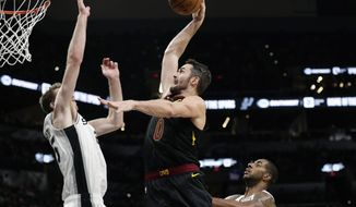 Cleveland Cavaliers forward Kevin Love (0) drives to the basket past San Antonio Spurs center Jakob Poeltl (25) during the second half of an NBA basketball game, in San Antonio, Thursday, Dec. 12, 2019. Cleveland won 117-109 in overtime. (AP Photo/Eric Gay)