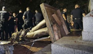 FILE - In this Aug. 20, 2018, file photo, police stand guard after the Confederate statue known as Silent Sam was toppled by protesters on campus at the University of North Carolina in Chapel Hill, N.C. The Lawyers' Committee for Civil Rights Under Law is warning University of North Carolina leaders that they should reconsider a $2.5 million settlement involving the statue of a Silent Sam. The Lawyers' Committee for Civil Rights Under Law has sent a letter encouraging UNC leaders to recover the money promised to the Sons of Confederate Veterans.  (AP Photo/Gerry Broome, File)