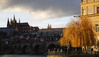 In this picture taken on Thursday, Nov. 28, 2019, tourists enjoy a view of the Prague Castle in Prague, Czech Republic. On Thursday, Dec. 12, Prague has approved a plan to sign a partnership agreement with the capital of Taiwan, Taipei. Mayor Zdenek Hrib said it focuses on economic, trade and cultural cooperation but not on politics. (AP Photo/Petr David Josek)