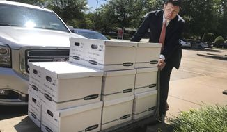 FILE - In this July 23, 2019, photo, Alex Gray, an attorney for Safe Surgery Arkansas, delivers petitions to the Arkansas secretary of state's office in favor of holding a referendum on a state law that expands the type of procedures optometrists can perform, in Little Rock, Ark. The Arkansas Supreme Court says thousands of signatures submitted in favor of holding a referendum on a new eye surgery law must be counted. The justices ruled Thursday, Dec. 12, 2019, that new ballot measure restrictions were incorrectly applied when election officials rejected the petitions submitted by opponents of the law that allows optometrists to perform several procedures that only ophthalmologists had been allowed to perform. (AP Photo/Andrew DeMillo, File)