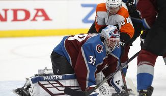 Colorado Avalanche goaltender Pavel Francouz, front, covers the puck after stopping a shot by Philadelphia Flyers center Scott Laughton in the second period of an NHL hockey game Wednesday, Dec. 11, 2019, in Denver. (AP Photo/David Zalubowski)