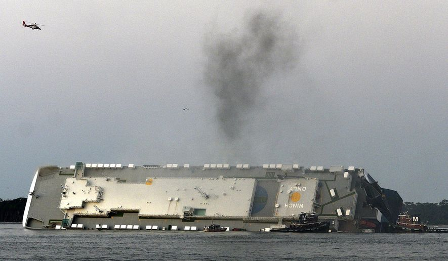 In a Sunday, Sept. 8, 2019 file photo, smoke rises from a cargo ship that capsized in the St. Simons Island, Georgia sound. Crews have finished draining all of the fuel from an overturned cargo ship three months after it capsized off the coast of Georgia, the team overseeing salvage operations said Thursday, Dec. 12, 2019. (Bobby Haven/The Brunswick News via AP, File) **FILE**