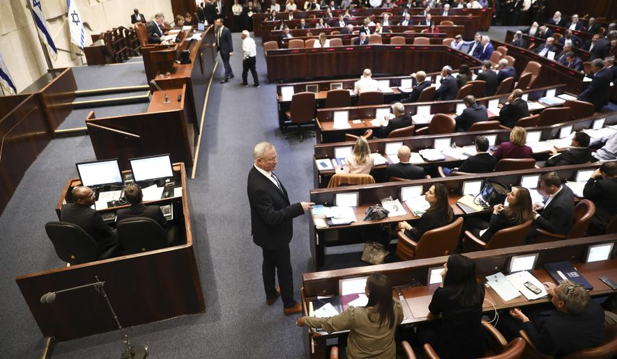 Blue and White party leader Benny Gantz, center, stands during a Knesset session in Jerusalem, Wednesday, Dec. 11, 2019. The Israeli parliament began voting to dissolve itself on Wednesday and pave the path to an unprecedented third election within a year. (AP Photo/Oded Balilty)