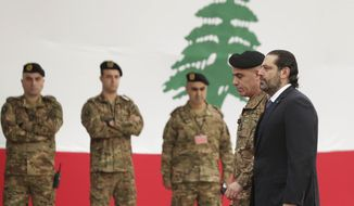 Resigned Lebanese Prime Minister Saad, right, arrives to attend a military parade to mark the 76th anniversary of Lebanon's independence from France at the Lebanese Defense Ministry, in Yarzeh near Beirut, Lebanon, Friday, Nov. 22, 2019. Lebanon's top politicians attended the military parade,  appearing for the first time since the government resigned amid nationwide protests now in their second month. (AP Photo/Hassan Ammar)