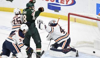 Minnesota Wild's Jordan Greenway, center, puts the puck past Edmonton Oilers goalie Mike Smith, right, for a goal in the first period of an NHL hockey game, Thursday, Dec.12, 2019, in St. Paul, Minn. (AP Photo/Tom Olmscheid)