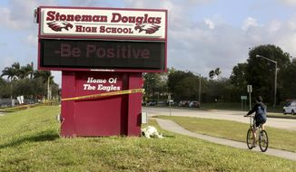 "FILE - In this Feb. 23, 2019 file photo, a bicyclist rides past a sign at Marjory Stoneman Douglas High School in Parkland, Fla.  A Florida grand jury looking into last year's Parkland school shooting chided schools, law enforcement and other local jurisdictions over continued ""turf wars"" that could hamper the response to another crisis. In a report released overnight, the statewide grand jury said the continued squabbling and other ""systemic"" failures were urgent enough for it to speak out before its term.  (Mike Stocker/South Florida Sun-Sentinel via AP, File)"