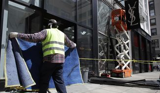 File - In this April 17, 2019, file photo, a work crew removes broken windows at a Yves Saint Laurent store in San Francisco, after a robber backed a car into a window and burglarized the store before fleeing. San Francisco authorities recovered about $2 million in suspected stolen electronics and clothing during a bust of what they called a sophisticated fencing operation, the district attorney's office announced Thursday, Dec. 12, 2019.  (AP Photo/Jeff Chiu, File)