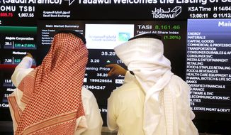 Saudi stock market officials watch the market screen displaying Saudi Arabia's state-owned oil company Aramco after the debut of Aramco's initial public offering (IPO) on the Riyadh's stock market in Riyadh, Saudi Arabia, Wednesday, Dec. 11, 2019. (AP Photo/Amr Nabil)
