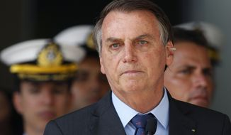With a band aid on his ear, Brazil's President Jair Bolsonaro attends a military ceremony in honor of Sailor Day, in Brasilia, Brazil, Friday, Dec. 13, 2019. Bolsonaro said to the press on Wednesday, Dec. 11, that he has a possible skin cancer after he had a mole removed from his ear. (AP Photo /Eraldo Peres)