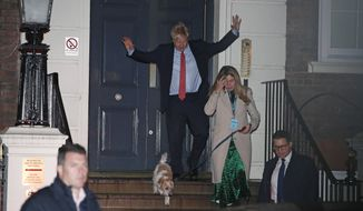 Britain's Prime Minister and Conservative Party leader Boris Johnson leaves Conservative Party headquarters with his partner Carrie Symonds and their dog Dilyn, in London, Friday, Dec. 13, 2019. Prime Minister Boris Johnson's Conservative Party appeared on course Friday to win a solid majority of seats in Britain's Parliament a decisive outcome to a Brexit-dominated election that should allow Johnson to fulfill his plan to take the U.K. out of the European Union next month. (AP Photo/Thanassis Stavrakis)