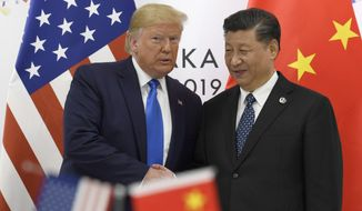In this June 29, 2019, file photo, U.S. President Donald Trump poses for a photo with Chinese President Xi Jinping during a meeting on the sidelines of the G-20 summit in Osaka, Japan. (AP Photo/Susan Walsh, File) **FILE**