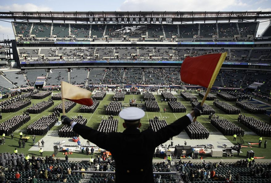 In this Dec. 8, 2018, file photo, Navy Midshipman Frey Pankratz singles his classmates as they march onto the field ahead of an NCAA college football against the Army in Philadelphia. The 120th Army-Navy game is set for Saturday in Philadelphia.  Navy leads the series 60-52-7. (AP Photo/Matt Rourke, File) **FILE**