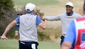 U.S. team player Justin Thomas, left, celebrates with his playing partner and captain, Tiger Woods, on the 18th green in their foursomes match during the President's Cup golf tournament at Royal Melbourne Golf Club in Melbourne, Friday, Dec. 13, 2019. (AP Photo/Andy Brownbill)