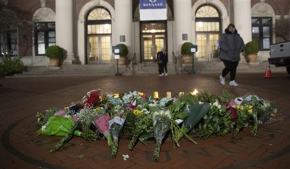 A woman walks past a make-shift memorial for Tessa Majors inside the Barnard College campus, Thursday, Dec. 12, 2019, in New York. Majors, a 18-year-old Barnard College freshman from Virginia, was fatally stabbed in a park near the school's campus in New York City. (AP Photo/Mary Altaffer)