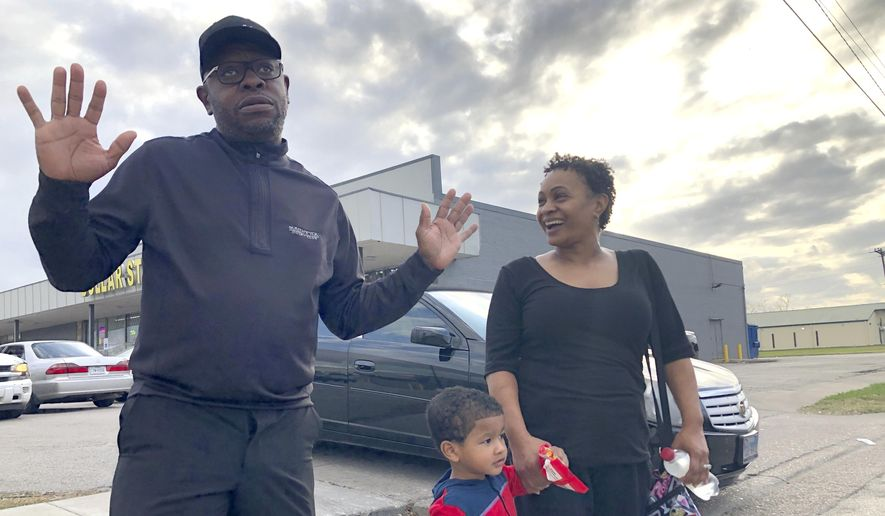 """In this Tuesday, Dec. 10, 2019, Rapper turned political candidate, Brad """"Scarface"""" Jordan, left, visits with voter Michele Lemon and her son outside of an early voting location in the Sunnyside neighborhood of Houston, Texas. Jordan is in a run-off against Carolyn Evans-Shabazz for a seat on the Houston City Council. (AP Photo/ John L. Mone)"""