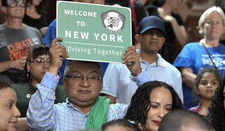 In this June 17, 2019, photo, a protester holds a sign as members of the state Assembly speak in favor of legislation of the Green Light Bill, granting undocumented immigrant driver's licenses during a rally at the state Capitol, in Albany, N.Y. The bill passed making New York the 13th state to authorize licenses for drivers without legal immigration status. On Monday, Dec. 16 license applicants without a valid Social Security number will be able to apply for a driver's license. An estimated 265,000 immigrants without legal documents are expected to get driver's licenses within three years, more than half of them in New York City, according to the Fiscal Policy Institute.(AP Photo/Hans Pennink) **FILE**