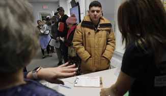In this Wednesday, Dec. 4, 2019 photo Helison Alvarenga, of Brazil, center, speaks with volunteers Marcia Previatti, front left, and Arlene Vilela, front right, at the New England Community Center, in Stoughton, Mass. Alvarenga, a 26-year-old from the Brazilian state of Minas Gerais, arrived in Massachusetts about four months ago after crossing the Mexican border at Juarez with his 24-year-old wife, Amanda, and 6-year-old son, David. The family were at the community center Dec. 4, to apply for new Brazilian passports, which Alvarenga says were seized by border officials. (AP Photo/Steven Senne)