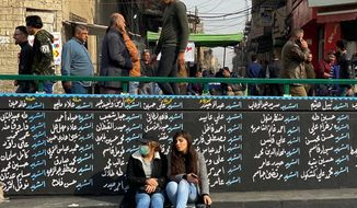Women sit by a wall with names of Anti-government protesters who have been killed in demonstrations in Tahrir Square during ongoing protests in Baghdad, Iraq, Thursday, Dec. 12, 2019. A gunman shot dead several people, including four protesters, Thursday provoking some anti-government demonstrators to disarm and hang him in a central Baghdad square, security and health officials said. The incident was condemned by the wider protest movement based in Tahrir Square, the epicenter of the movement, who said the individuals who killed the gunman were not part of their peaceful demonstrations. (AP Photo/Khalid Mohammed)