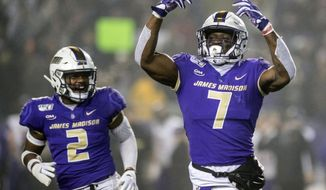 James Madison defensive lineman John Daka (7), right, and linebacker Dimitri Holloway (2) celebrate after making a sack during the first half of a quarterfinal game against Northern Iowa in the NCAA college Football Championship Subdivision playoffs in Harrisonburg, Va., Friday, Dec. 13, 2019. (Daniel Lin/Daily News-Record via AP) ** FILE **