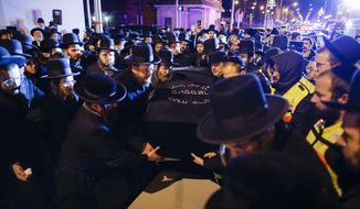 Orthodox Jewish men carry the casket with Mindel Ferencz who was killed in a kosher market that was the site of a gun battle in Jersey City, N.J., Wednesday, Dec. 11, 2019. Ferencz, 31, who with her husband owned the grocery store. The Ferencz family had moved to Jersey City from Brooklyn. (AP Photo/Eduardo Munoz Alvarez)