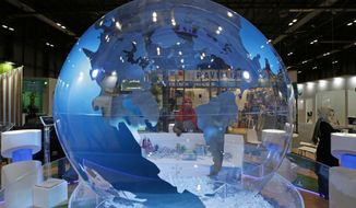 A woman looks at a World globe at the COP25 climate talks congress in Madrid, Spain, Friday, Dec. 13, 2019. Officials from almost 200 countries are scrambling to reach an agreement at a United Nations climate meeting amid growing concerns that key issues may be postponed for another year. (AP Photo/Paul White)