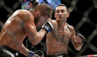 FILE - In this Dec. 12, 2015, file photo, Max Holloway, right, fights Jeremy Stephens during a featherweight mixed martial arts bout at UFC 194 in Las Vegas. Holloway and Amanda Nunes are among the toughest and winningest fighters of their generation, and their latest title defenses against Alex Volkanovski and Germaine De Randamie are both likely to be more entertaining than the main event bout between two wrestlers who sometimes talk better than they punch. (AP Photo/John Locher, File)