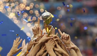 FILE - In this July 7, 2019, file photo, the United States players hold the trophy as they celebrate winning the Women's World Cup final soccer match against The Netherlands at the Stade de Lyon in Decines, outside Lyon, France. FIFA has received bids from Brazil, Japan, Colombia and a joint bid from Australia and New Zealand to host the 2023 Women's World Cup on Friday, Dec. 13, 2019. (AP Photo/Francisco Seco, File)