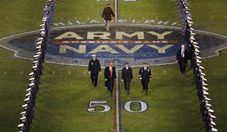 President Donald Trump and Secretary of Defense Mark Esper cross the field after the first half of an NCAA college football game between Army and Navy, Saturday, Dec. 14, 2019, in Philadelphia. (AP Photo/Matt Rourke)