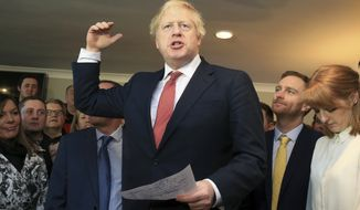Britain's Prime Minister Boris Johnson, gestures as he speaks to supporters on a visit to meet newly elected Conservative party MP for Sedgefield, Paul Howell, at Sedgefield Cricket Club in County Durham, north east England, Saturday Dec. 14, 2019, following his Conservative party's general election victory.  Johnson called on Britons to put years of bitter divisions over the country's EU membership behind them as he vowed to use his resounding election victory to finally deliver Brexit. (Lindsey Parnaby/Pool via AP)