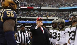 President Donald Trump throws the coin in the air before the start of the Army-Navy college football game in Philadelphia, Saturday, Dec. 14, 2019. (AP Photo/Jacquelyn Martin)  **FILE**