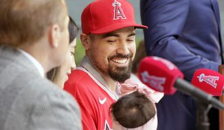 Los Angeles Angels' Anthony Rendon looks over at his 17-month-old daughter, Emma during a news conference to welcome him to the baseball team in Anaheim, Calif., Saturday, Dec. 14, 2019. (AP Photo/Alex Gallardo) **FILE**