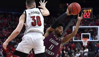 Eastern Kentucky guard Jomaru Brown (11) attempts to pass the ball as Louisville guard Ryan McMahon (30) defends during the first half of an NCAA college basketball game in Louisville, Ky., Saturday, Dec. 14, 2019. (AP Photo/Timothy D. Easley)