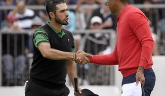 U.S. team player and captain Tiger Woods, right, shakes hands with International team player Abraham Ancer of Mexico after Woods won their singles match 3 and 2 during the President's Cup golf tournament at Royal Melbourne Golf Club in Melbourne, Sunday, Dec. 15, 2019. (AP Photo/Andy Brownbill)