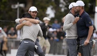 International team players Louis Oosthuizen of South Africa, second left, Abraham Ancer of Mexico, left, Adam Scott of Australia and Marc Leishman of Australia, right, celebrate on the 18th green after their foursome matches during the President's Cup golf tournament at Royal Melbourne Golf Club in Melbourne, Saturday, Dec. 14, 2019. (AP Photo/Andy Brownbill)