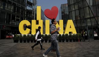 "FILE - In this Sept. 29, 2019, file photo, a man eats a snack while passing an ""I love China"" decoration at a popular shopping mall in Beijing. China is putting a positive face on an agreement to start dialing down a trade war that it blames the U.S. for starting. Chinese experts and news media said Saturday that the deal would reduce uncertainty for companies and lay the foundation for further talks. (AP Photo/Andy Wong)"