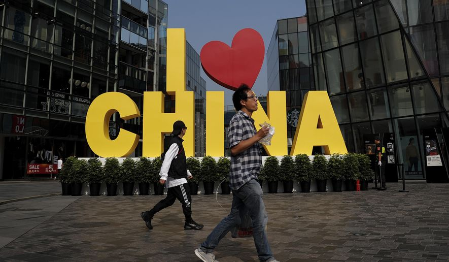 """FILE - In this Sept. 29, 2019, file photo, a man eats a snack while passing an """"I love China"""" decoration at a popular shopping mall in Beijing. China is putting a positive face on an agreement to start dialing down a trade war that it blames the U.S. for starting. Chinese experts and news media said Saturday that the deal would reduce uncertainty for companies and lay the foundation for further talks. (AP Photo/Andy Wong)"""