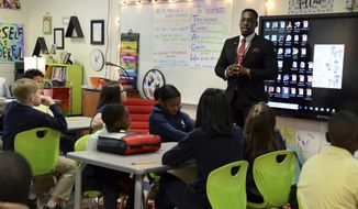 This Dec. 5, 2019 photo,  Nnamdi Onyekwuluje, case manager for the School-Justice Partnership program in Macon-Bibb County, talks to a fifth grade class at Springdale Elementary School about making good decisions as they go into middle school.   The School-Justice Partnership program offers students, who commit minor offenses, an alternative to getting suspended, expelled or arrested. They are instead referred to services in the community, such as counseling, mediation, tutoring and community workshops. (Jenna Eason/The Macon Telegraph via AP)