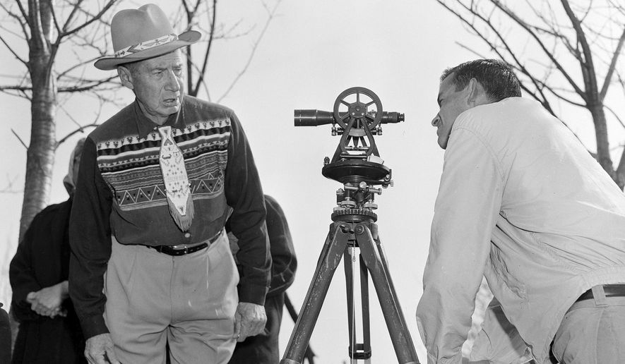 In this April 18, 1958 file photo, Philip N. Brooks, right, a New York State surveyor, takes a look through his transit on the Tuscarora Indian Reservation near Niagara Falls, N.Y., while Tuscarora Chief Elton Black Cloud Greene watches. The tribe is resisting state seizure of their land for a power project. In 1959, the U.S. government started the switch from the U.S. survey foot to the international foot, and it will finish the job in 2022. (AP Photo)