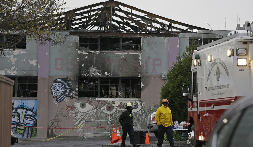 FILE - This Dec. 7, 2016 file photo shows Oakland fire officials walk past the remains of the Ghost Ship warehouse damaged from a deadly fire in Oakland, Calif. Anger over plans for a television series about a deadly warehouse fire in the San Francisco Bay Area has led husband-and-wife authors Michael Chabon and Ayelet Waldman to scuttle the project for now. The Berkeley, California-based couple said Saturday, Dec. 14, 2019, that since word got out that they were in the early stages of developing a New York Times Magazine article about the 2016 fire at the Ghost Ship warehouse for TV, many friends and families of the victims have urged them to reconsider the project because it was too soon for them to relive the tragedy. (AP Photo/Eric Risberg, File)