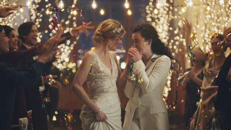 This image made from undated video provided by Zola shows a scene of its advertisement. Under pressure from a conservative advocacy group, The Hallmark Channel has pulled the ads for wedding-planning website Zola that featured same-sex couples, including two brides kissing. The family-friendly network, which is in the midst of its heavily watched holiday programming, removed the ads because the controversy was a distraction, a spokesperson said in an interview on Saturday, Dec. 14, 2019. (Zola via AP)